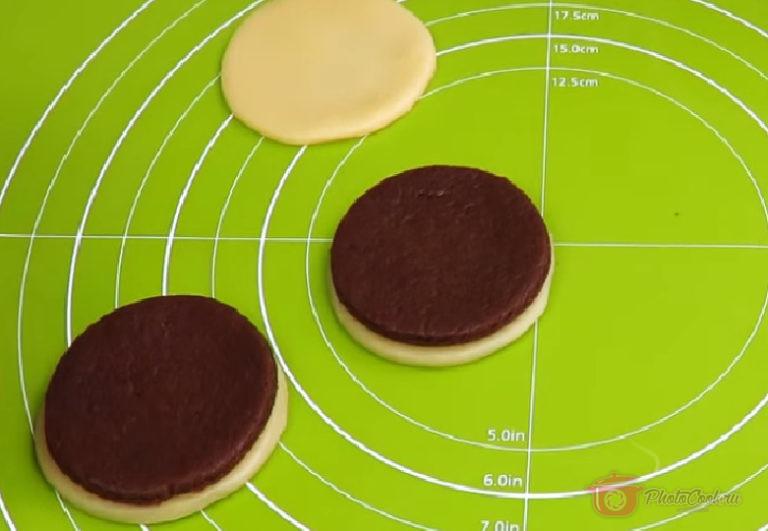 На каждый кружочек белого теста выкладываем кружочек шоколадного. Разрезаем пополам.
