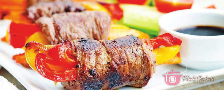 Выложите поперёк полосок говядины овощи.Сверните рулетики, закрепите их зубочистками. Обжарьте…